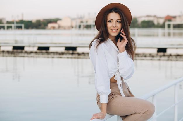 Une femme élégante, parlant par téléphone et marchant le long du front de mer sur une chaude journée d'été au coucher du soleil Photo Premium