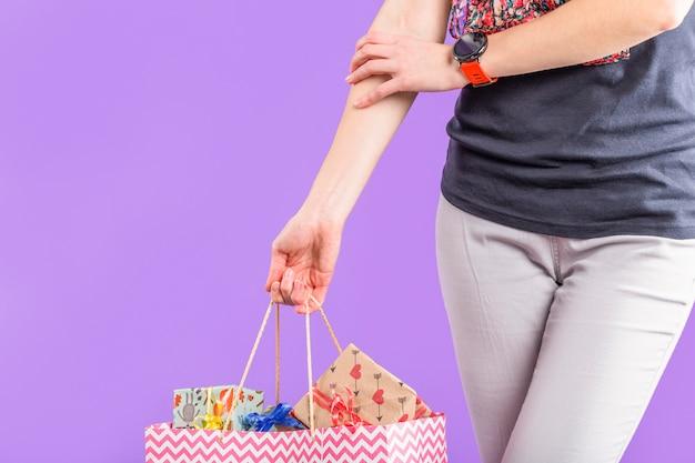 Femme élégante Portant Un Sac En Papier Avec Des Coffrets Cadeaux Emballés Contre Du Papier Peint Violet Photo gratuit