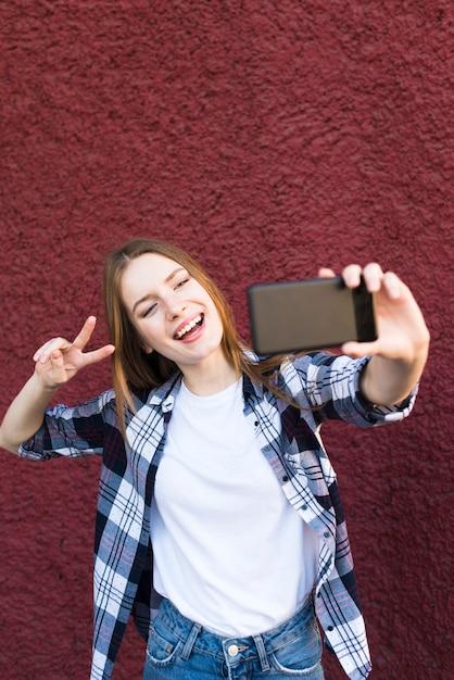 Femme élégante prenant selfie avec geste de signe de paix Photo gratuit