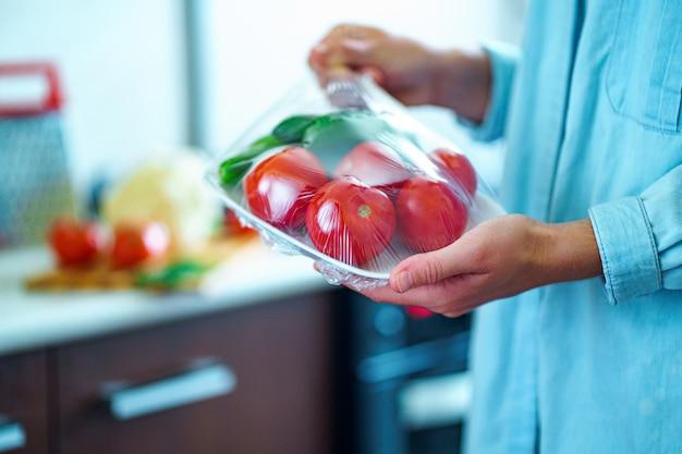 Femme Emballé Des Légumes Frais à L'aide D'un Film Alimentaire Pour Le Stockage Des Aliments Dans Le Réfrigérateur Photo Premium