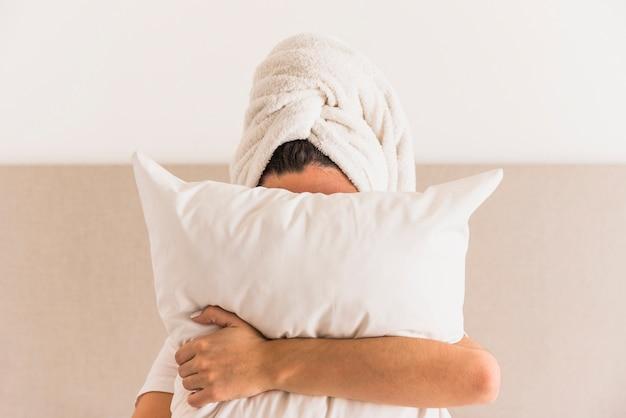 Femme, emballer, tête, serviette, tenue, oreiller blanc, devant, elle, visage Photo gratuit