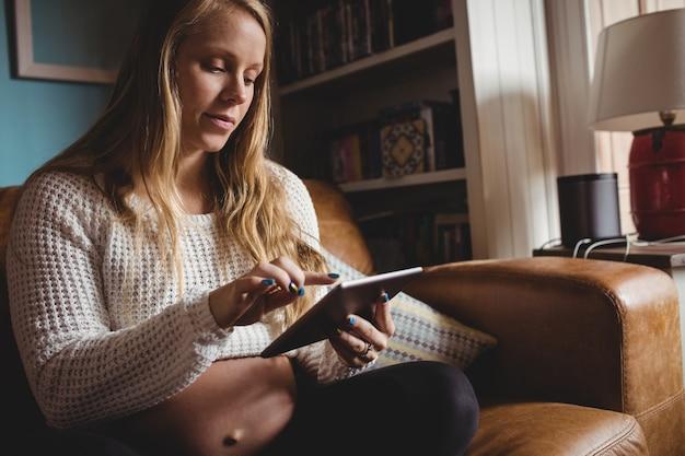 Femme enceinte à l'aide de tablette numérique dans le salon Photo gratuit