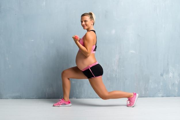 Femme enceinte blonde faisant du sport en haltérophilie Photo Premium