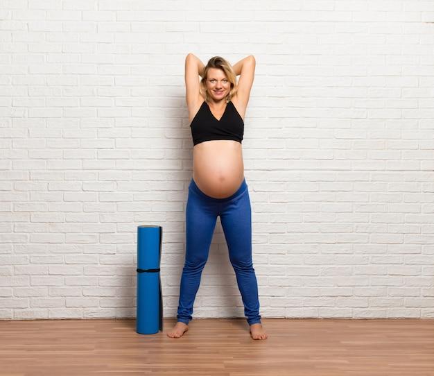 Femme enceinte blonde faisant des exercices à l'intérieur en haltérophilie Photo Premium