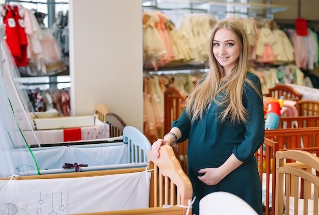 Une femme enceinte choisit un lit bébé dans le magasin. Photo Premium