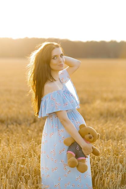 Une Femme Enceinte Dans Une Longue Robe Bleue Dans Un Champ De Blé Au Coucher Du Soleil Tenant Un Ours En Peluche Et Souriant Photo Premium