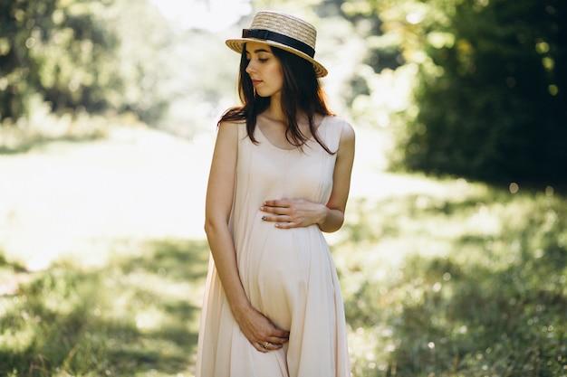 Femme enceinte dans parc Photo gratuit