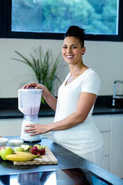 Femme Enceinte Debout Dans La Cuisine Et Prépare Des Jus De Fruits Dans Un Mélangeur Photo Premium
