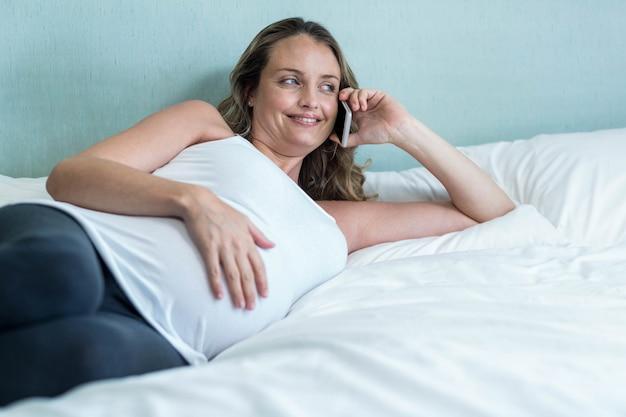 Femme enceinte faisant un appel téléphonique sur son lit Photo Premium