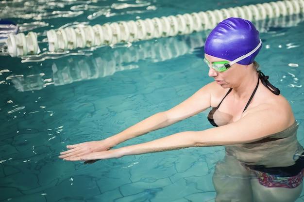 Femme enceinte faisant de l'exercice dans la piscine du centre de loisirs Photo Premium