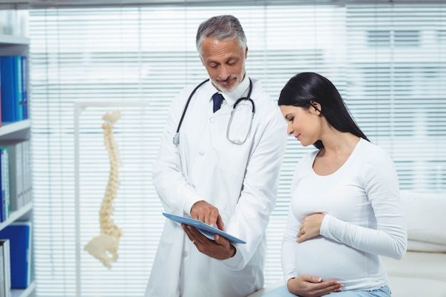 Femme enceinte en interaction avec un médecin en clinique Photo Premium