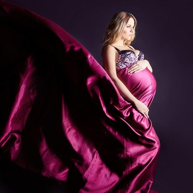 Femme enceinte en lingerie sur fond gris Photo Premium
