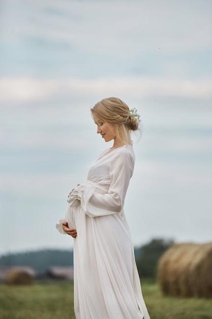Femme Enceinte Marche Dans Un Champ Près De Meules De Foin Dans Une Longue Robe Blanche Photo Premium