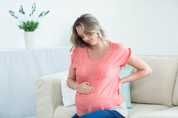 Femme enceinte avec maux de dos dans le salon Photo Premium