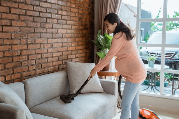 Femme Enceinte Nettoyage Canapé Avec Aspirateur Photo Premium