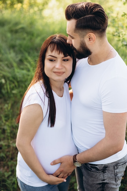 Femme enceinte et son mari aux cheveux étreignant sur le ventre ensemble dans la nature en plein air Photo Premium