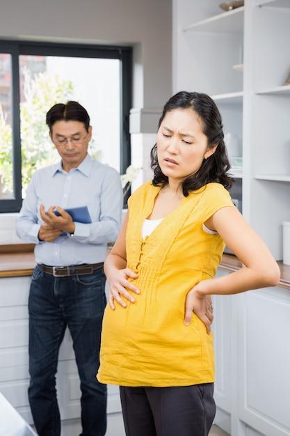 Femme enceinte souffrant de maux de dos dans les ktichen Photo Premium