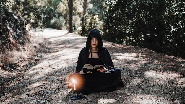 Femme enchanteur avec livre et chandelier assis sur un chemin forestier Photo gratuit