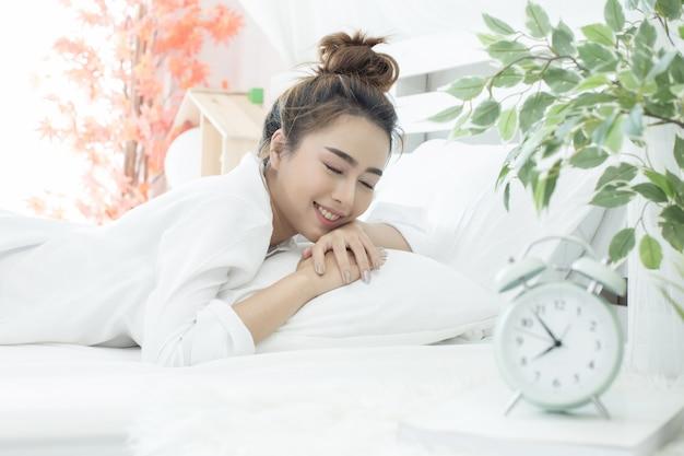 Femme Endormie Dans Son Lit Pendant Que Son Réveil Indique L'heure à La Maison Dans La Chambre Photo gratuit