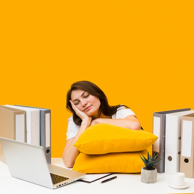 Femme Endormie Avec Des Oreillers Sur Son Bureau Photo gratuit