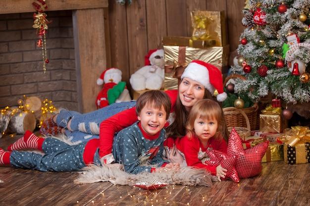 Femme Avec Enfants Allongée Sur La Peau Dans Un Bonnet De Noel à Côté De L'arbre De Noël Photo Premium