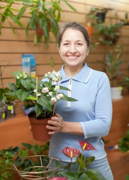 Femme entourée de différentes fleurs au magasin de fleurs Photo gratuit