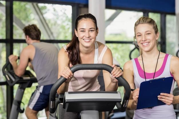 Femme entraîneur parlant avec une femme faisant du vélo au gymnase Photo Premium