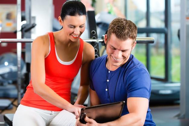 Femme et entraîneur personnel dans une salle de sport Photo Premium