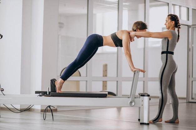 Femme, entraîneur pilates, pratiquer pilates Photo gratuit