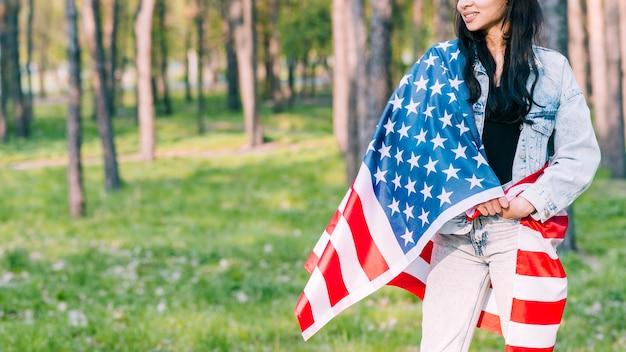 Femme enveloppée dans le drapeau américain dans le parc Photo gratuit