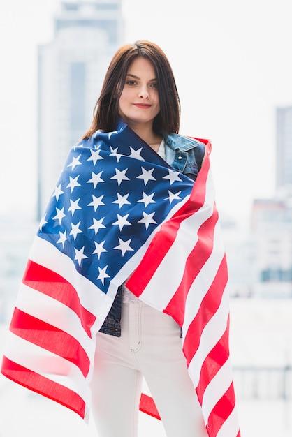 Femme enveloppée dans le drapeau des états-unis Photo gratuit
