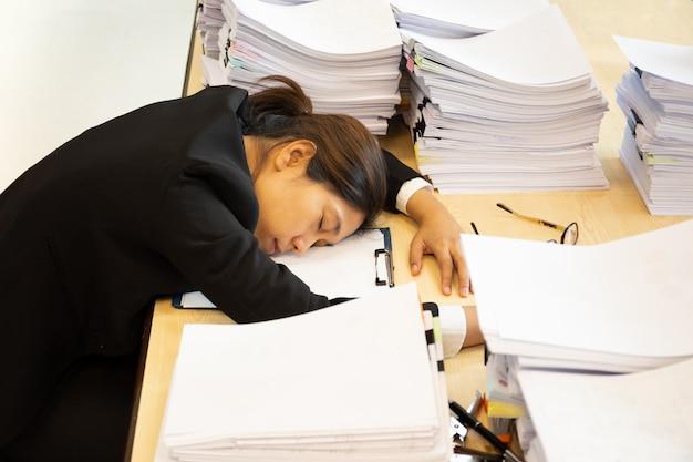 Une femme épuisée a beaucoup de travail avec des documents qui s'endorment sur son bureau. Photo Premium