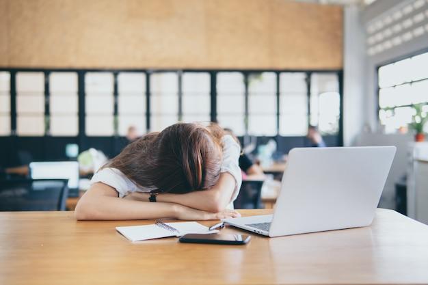 Femme épuisée frustrée tête sur table. concept de finance et d'affaires de réalisation Photo Premium