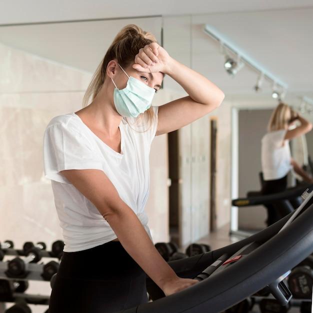 Femme épuisée Avec Masque Médical à La Salle De Sport Photo Premium