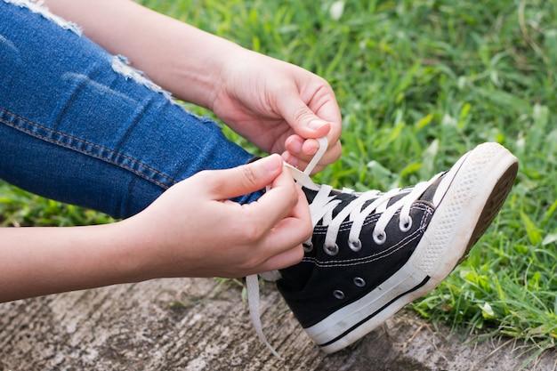 Femme essayant de lacer ses baskets Photo Premium