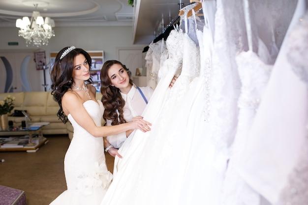 Femme essayant la robe de mariée dans un magasin avec une assistante féminine. Photo Premium