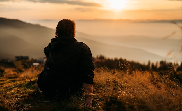 Une Femme Est Assise Au Sommet D'une Montagne En Attendant Que Le Soleil Se Lève. Photo Premium