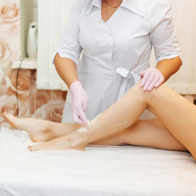 Femme esthéticienne dans la procédure de l'épilation sur les jambes d'une fille avec l'épilation au sucre Photo Premium