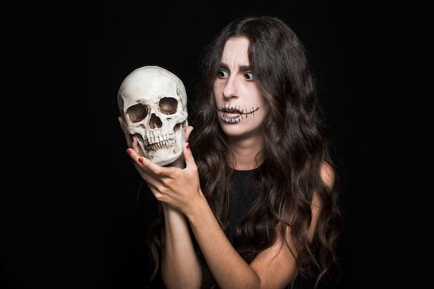Femme étonnée tenant crâne Photo gratuit