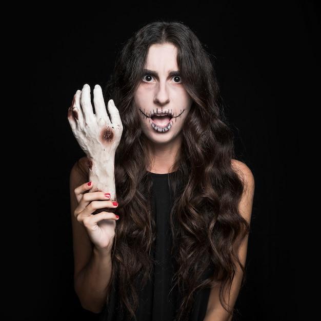 Femme étonnée tenant la main morte Photo gratuit