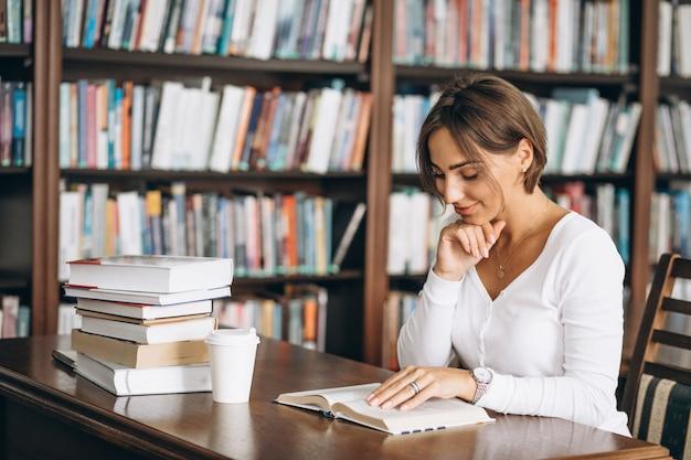 Femme étudiante à la bibliothèque Photo gratuit