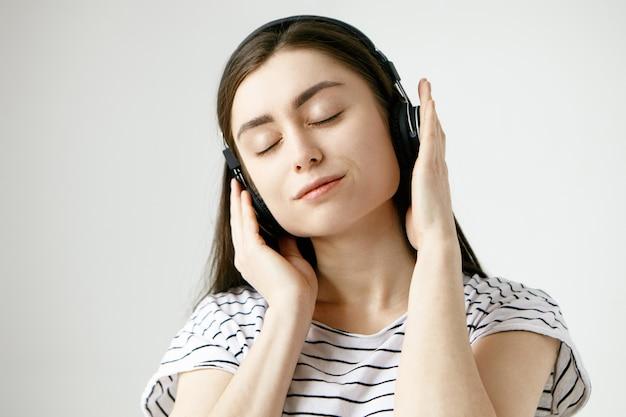 Femme étudiante Brune Posant Les Yeux Fermés, écoutant Des Sons Méditatifs Calmes De La Nature Ou Des Pistes Ambiantes à L'aide D'un Casque Photo gratuit