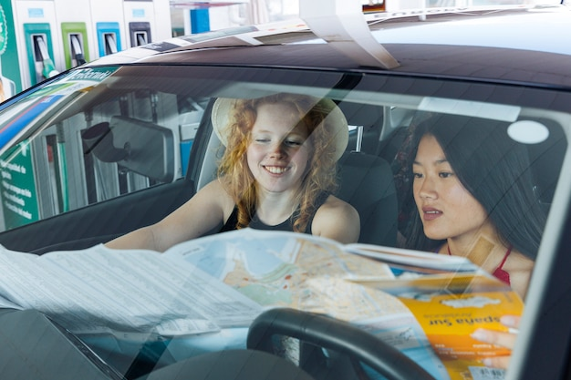 Femme, étudier, carte route, reposer dans voiture Photo gratuit