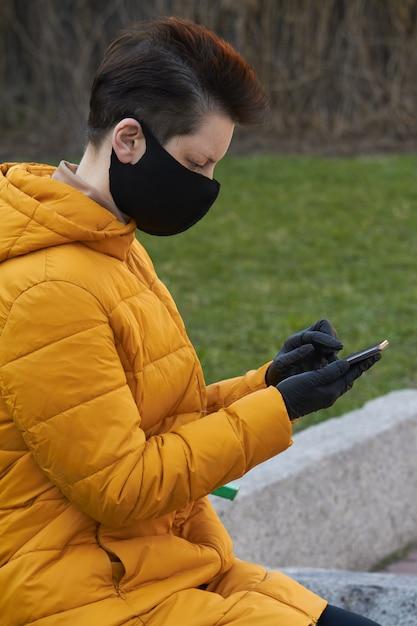 Femme Européenne D'âge Moyen En Masque De Protection Noir Et Gants Tenant Un Smartphone à L'extérieur Pendant L'épidémie De Coronavirus Covid-19 Photo Premium