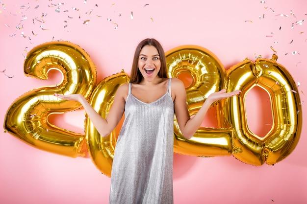 Femme Excitée Avec Des Confettis D'argent Et Ballons Dorés Du Nouvel An 2020 Isolés Sur Rose Photo Premium