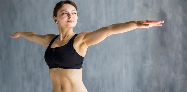 Femme exécutant une extension de bras latérale Photo gratuit