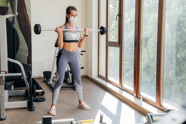 Femme Exerçant à La Salle De Gym Avec équipement Et Masque Photo gratuit