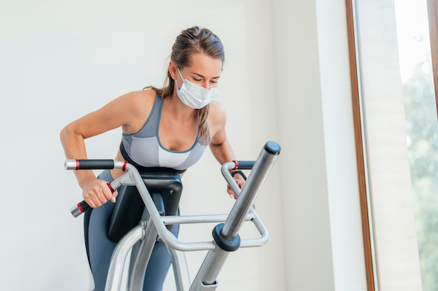 Femme Exerçant à La Salle De Gym Avec Masque Et équipement Photo gratuit