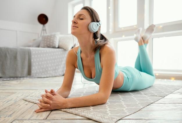 Femme Exerçant Sur Tapis Et écouter De La Musique Photo gratuit