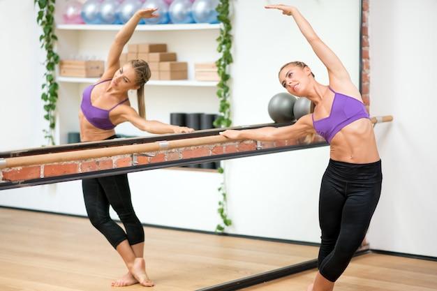 Femme, exercice, barre, côté, stretch, à, gym Photo Premium